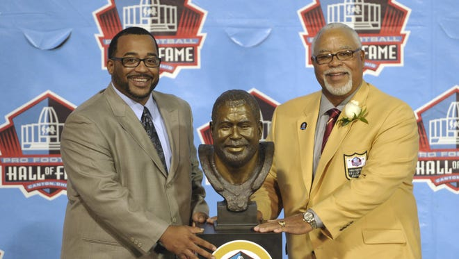 Inductee Curley Culp, right, poses with his presenter, his son Chad Culp, and a bust of himself during the induction ceremony at the Pro Football Hall of Fame Saturday, Aug. 3, 2013, in Canton, Ohio.
