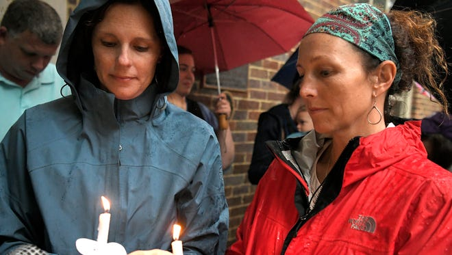 Franklin residents Katie Haseltine and Stacey Perry light candles for a Stand in Solidarity with Charlottesville peace rally on the downtown square in Franklin on Monday, Aug. 14, 2017.