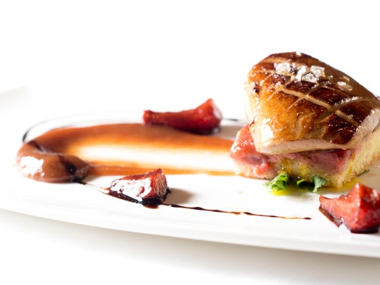 Seared foie gras, a signature dish at Charlie Palmer Steak, rests atop a strawberry-rhubarb crisp. Spring 2015 marks the debut of this version of foie gras.
