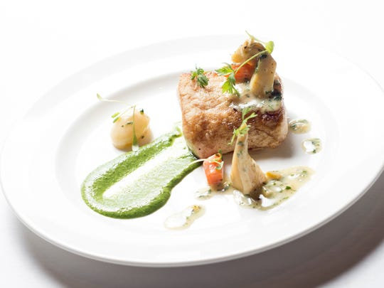 Halibut, a classic fish of spring, is pan roasted and spooned with braised baby artichoke ragoût.