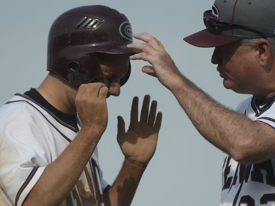 Genoa's Matt Aumiller tries to get the dust out of his eyes after sliding into second.