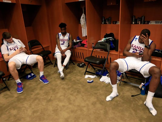 Kansas' Sviatoslav Mykhailiuk, left, Lagerald Vick and Dwight Coleby, right, sit in the locker room after the team's Midwest Regional final against Oregon in the NCAA men's college basketball tournament, Saturday, March 25, 2017, in Kansas City, Mo. Oregon won 74-60. (AP Photo/Orlin Wagner)