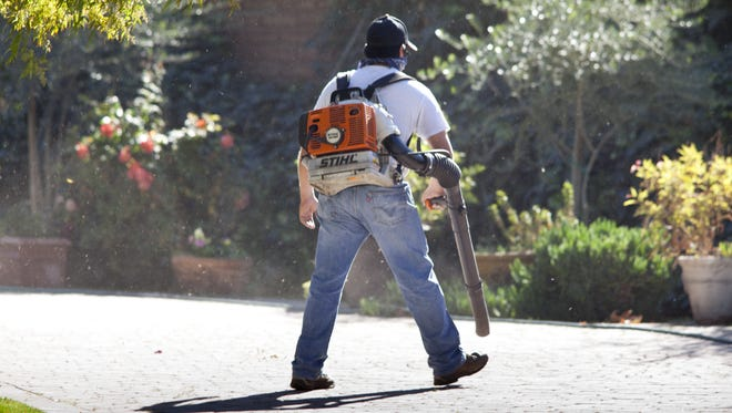 A landscaping crew member uses a leaf blower on a job in the Encanto area of central Phoenix.