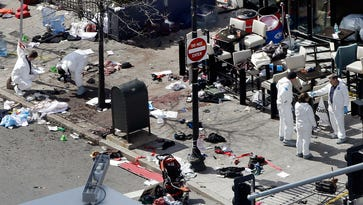 In this April 16, 2013, file photo, investigators examine the scene of the second bombing outside the Forum Restaurant on Boylston Street near the finish line of the 2013 Boston Marathon.