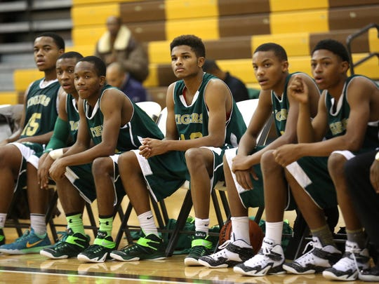 Crispus Attucks players watch the action from the bench  during a scrimmage against Howe Nov. 21, 2014.