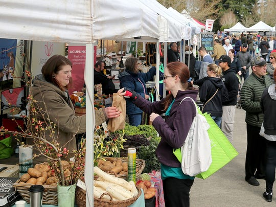 Chelsea Esterline of Silverdale (center) buys potatoes from Megan Thierry of Dharma Ridge Farm in Quilcene at the Poulsbo Farmers Market on Saturday. The market had a steady flow of customers at its new location.