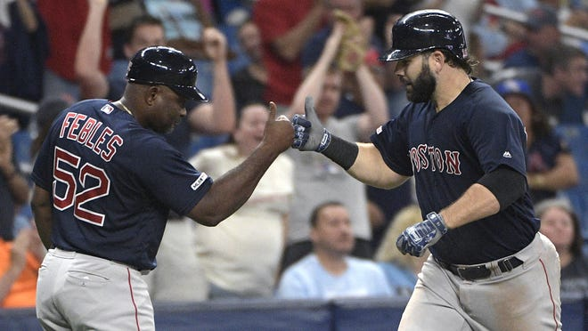 Boston Red Sox third-base coach Carlos Febles (52), shown congratulating Mitch Moreland on a two-run home run against the Tampa Bay Rays in a previous season, did not travel with the team to Tampa but was sent home to Boston from New York after an an inconclusive coronavirus test result.