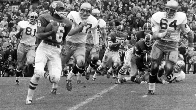 In a photo provided by the Michigan State University, Jimmy Raye carries the ball against the Notre Dame defense in East Lansing on Nov. 19, 1966. The game finished in a 10-10 tie.