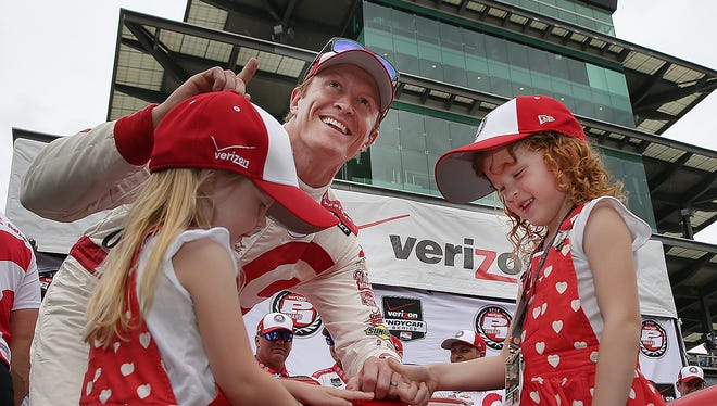 Scott Dixon, along with his daughter Tilly,left, and Poppy celebrates winning the pole position for the 99th Indianapolis 500 Sunday, May 17, 2015, morning at the Indianapolis Motor Speedway.