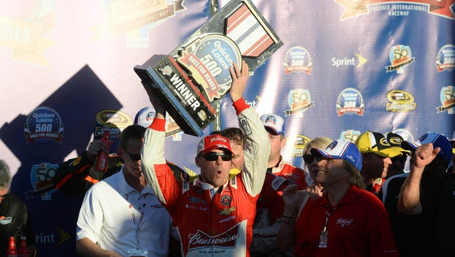 NASCAR Sprint Cup Series driver Kevin Harvick (front) celebrates with the trophy after winning the Quicken Loans Race For Heroes 500 at Phoenix International Raceway on Sunday.