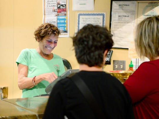Ellie Feinroth, co-owner of Doc Chey's Noodle House, rings up customers at the front register during lunch service on Thursday, Aug. 3, 2017.