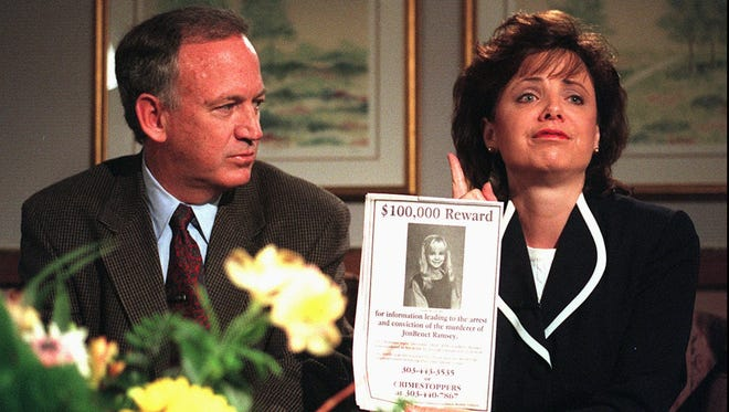 John Ramsey looks on as his wife, Patsy, holds an advertisement promising a reward for information leading to the arrest and conviction of the murderer of their 6-year-old daughter, JonBenet, in this May 1, 1997 file photo, in Boulder, Colo.