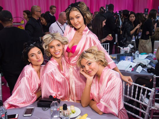 Jacquelyn Jablonski visits a table of models, from left, Devon Windsor, Gigi Hadid and Rachel Hilbert backstage in hair and makeup at the 2015 Victoria's Secret Fashion Show.