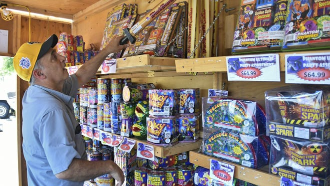 Rick Krikorian, of Sequoia Triple X Fraternity, gets the club's firework booth on Akers Street and Goshen Avenue ready to sell. The booth is one of many locations to buy safe and sane fireworks in Visalia.