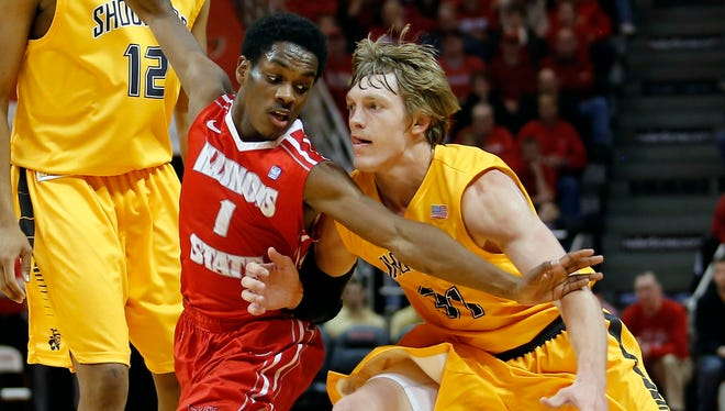 Illinois State guard Paris Lee (1) reaches in to defend against Wichita State guard Ron Baker (31) during the second half of an NCAA college basketball game at Redbird Arena, Wednesday, Jan. 22, 2014, in Normal, Ill. Wichita State won the game 70-55.