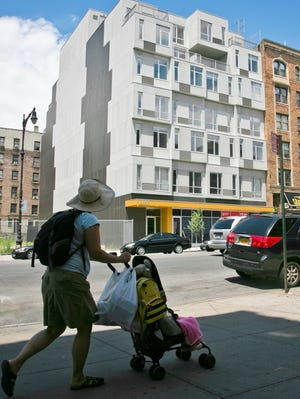 A seven-story modern modular apartment building called the Stack, center, is shown next to a decades-old residence, on  July 9,  in the Innwood neighborhood of New York. The Stack's 28 apartments were formed from 59 modules of rectangular components all 12.5 feet wide and 50 to 60 feet long. It's billed as the first multistory, modular-built apartment building to open in the city.