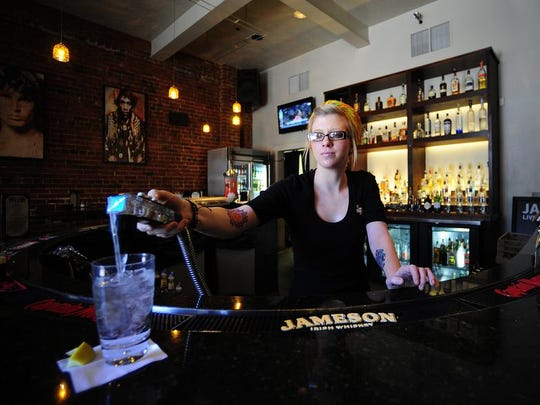 Server Kylin Jordan pours a drink in the bar at Jefferson Street Pub in Lafayette. The bar will be hosting a Festival International de Louisiane preview party Thursday.