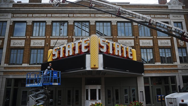 Scott Dangel, left, and Travis Cole, both with Pride Neon Sign Company, install a Daktronics Galaxy display onto the State Theatre sign Wednesday, Sept. 7, 2016, in downtown Sioux Falls.