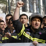 In this 2010 file photo, firefighters chant slogans outside the Greek Parliament during a protest in central Athens.