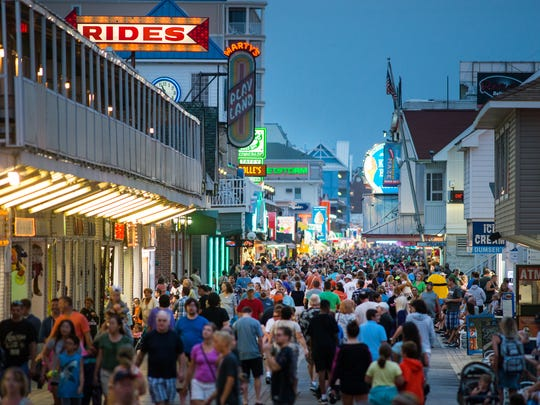 As nighttime draws near, the Ocean City Boardwalk is lit up and bustling.
