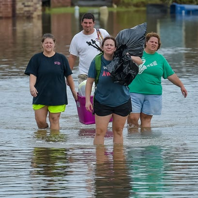 People make their way through a flooded area in Youngsville, Louisiana, on Aug. 14.. More than 100,000 people in Louisiana have registered for federal emergency aid.