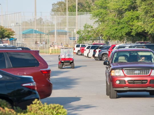 A golf cart makes its way through the parking lot at Shoreline Park in Gulf Breeze on April 10.