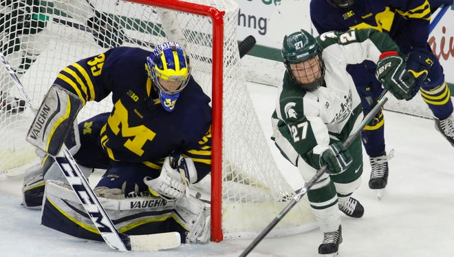 Michigan State's Matt Berry (27) looks to shoot against Michigan goalkeeper Zach Nagelvoort during the third period of an NCAA college hockey game, Friday in East Lansing.
