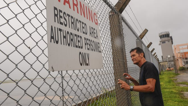 Benny Crawford, an ancestral land landowner, peers through the perimeter fence of the A.B. Won Pat International Airport in 2014. Crawford and other families of the original landowners, have land parcels in Tiyan that are being used or controlled by the airport authority.