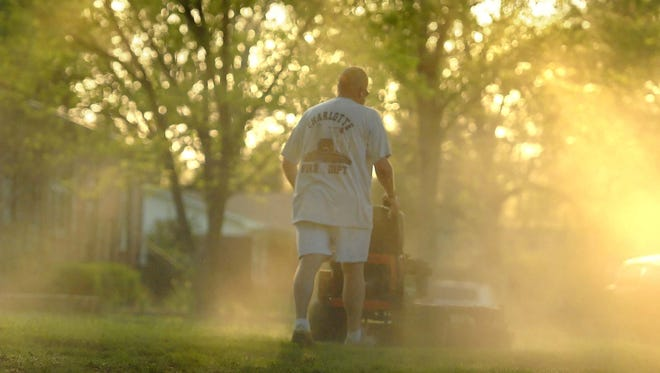 A cloud of pollen is kicked up by a homeowner mowing his lawn in Charlotte, N.C. . Everywhere, it seems, is covered in a fine yellow dust that irritates our lives. (AP Photo/The Charlotte Observer, Todd Sumlin) ORG XMIT: NCCHN201