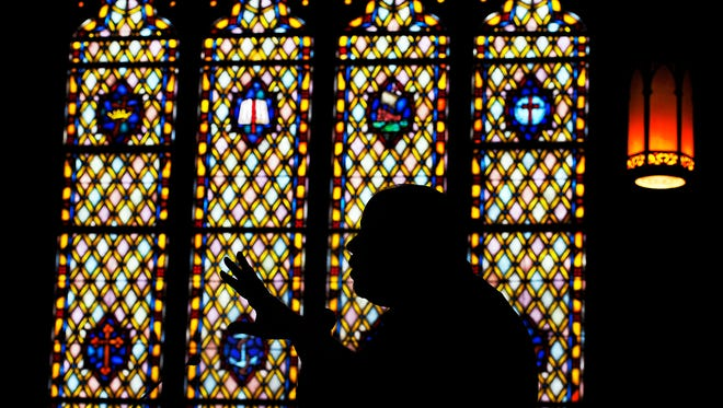 Dr. Jim Tartella a member of Jackson Street Baptist Church, speaks at the altar about the history of the many stained glass windows at the church in Scranton, Pa.,  on Saturday, during a tour. The church was built in 1890.