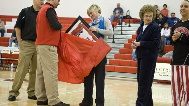 Natalie Winkelfoos, Bucyrus High School class of 1999, gets a hand from former Bucyrus Athletics Director Tom Jeffrey as she opens a sign commemorating her career and achievement as the first Bucyrus basketball player to score one thousand points in a career.
