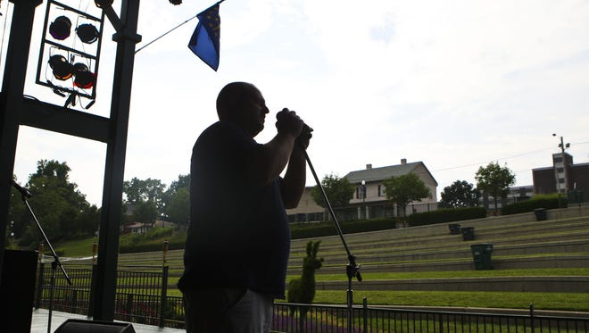 John Heal helps set up the microphones before a Friday night concert at Jeffersonville's Riverstage. The floating stage has become a place where bands are performing on Friday nights during the summer months. Seating is tiered grass steps and topiary abounds. June 11, 2010