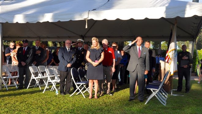 """File: Ret. U.S. Air Force Sgt. David Grossi salutes and others place their hands over their hearts as """"Taps"""" is played at the conclusion of a Patriot Day service in Bonita Springs."""