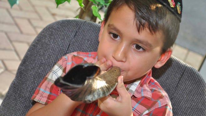 Kanaloa Acol, 6, blows his newly made shofar during the Shofar Factory event at Chabad Bonita Springs & Estero Sept. 15.
