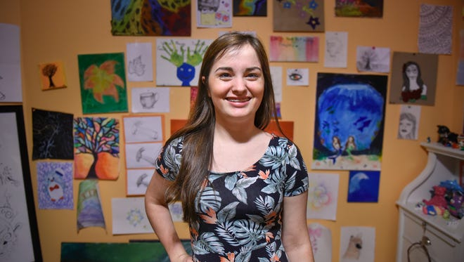 Grace Grell smiles in front of a small collection of her paintings Nov. 15, 2016 at her home in St. Cloud. Grell is selling some of her artwork to raise money for the Make-A-Wish Foundation.