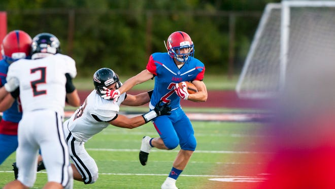 St. Clair's Ethan Mahn is brought down by a player from Marine City during their game Sept. 29.