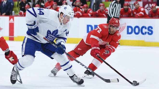 Maple Leafs defenseman Morgan Rielly (44) takes the puck up ice as Red Wings left wing Andreas Athanasiou (72) breaks up the play during the first period on Sunday, Feb. 18, 2018, at Little Caesars Arena.