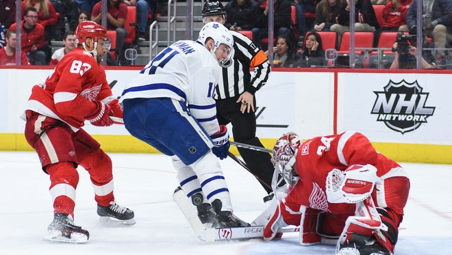 Red Wings goaltender Petr Mrazek (34) makes a save as Maple Leafs center Zach Hyman (11) attempts to score during the third period of the Wings' 3-2 loss on Sunday, Feb. 18, 2018, at Little Caesars Arena.