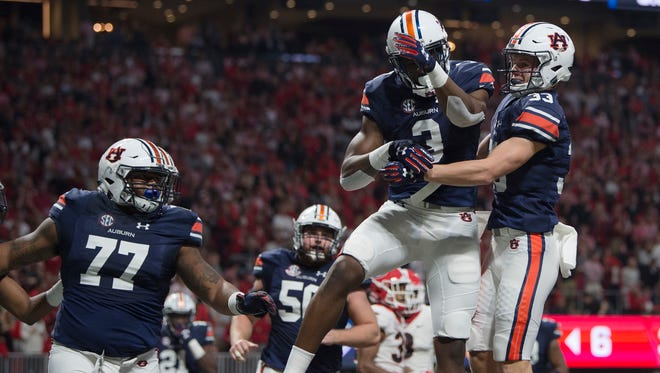 Auburn wide receiver Will Hastings (33) celebrates with Auburn wide receiver Nate Craig-Myers (3) after he scored a touchdown during the SEC Championship Football Game at the Mercedes-Benz Stadium in Atlanta, GA., in Saturday, Dec. 2, 2017.