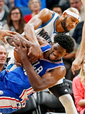 The Minnesota Timberwolves' Adreian Payne, top, tries to wrestle the ball from the Philadelphia 76ers' Joel Embiid on Nov. 17, 2016, in Minneapolis.