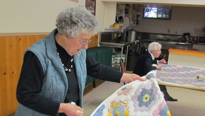 Edna Rickman, a founding member of Sublimity Quilters, examines a quilt finished by Lois Stiles as the group prepares for the Annual Quilt Week in 2014 at St. Boniface Rectory Basement Hall.