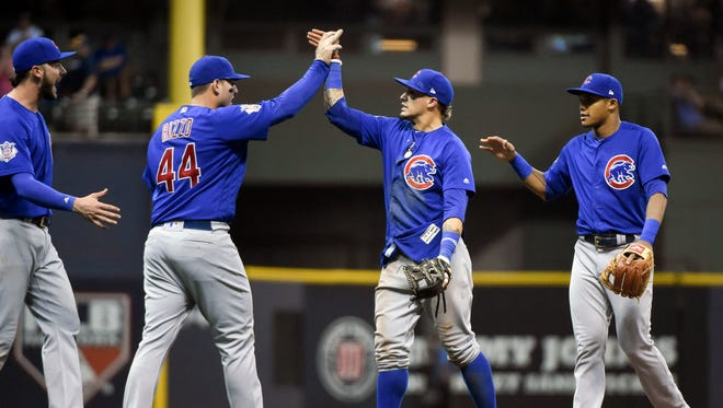 Cubs players, from left to right, Kris Bryant, Anthony Rizzo, Javier Baez and Addison Russell celebrate after beating the Brewers in 10 innings at Miller Park in Milwaukee.