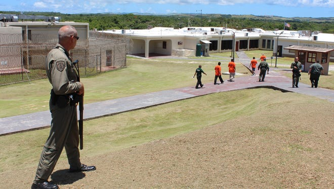 In this file photo, Department of Corrections officers keep their eyes on inmates walking through the yard at the Mangilao prison.