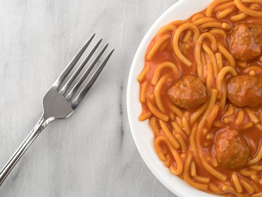 Plate of spaghetti and meatballs with fork on marble