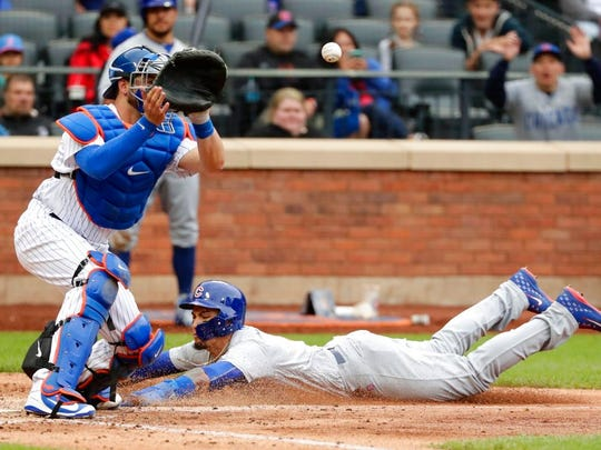 Chicago Cubs' Javier Baez, right, slides past New York Mets catcher Kevin Plawecki to steal home during the seventh inning of a baseball game Sunday, June 3, 2018, in New York.