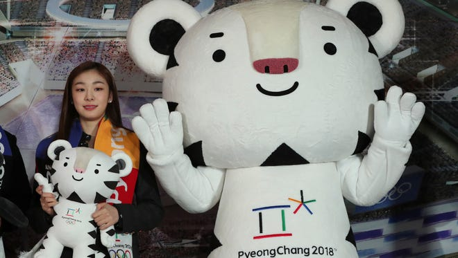 """Figure skating Olympics gold medalist Yuna Kim, an honorary ambassador for the 2018 Winter Olympics, poses with an official mascot of the 2018 Pyeongchang Olympic Winter Games, white tiger """"Soohorang"""" in February."""