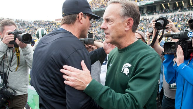 Michigan head coach Jim Harbaugh, left, and Michigan State head coach Mark Dantonio shake hands after the game.