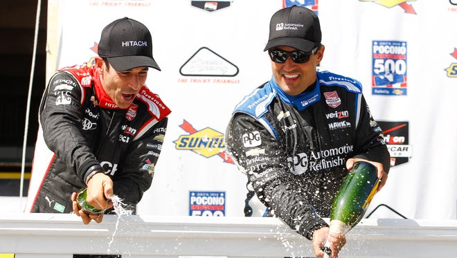 Race winner Juan Pablo Montoya, right, and Team Penske teammate Helio Castroneves celebrate their 1-2 finish at the Pocono IndyCar 500 on July 6.
