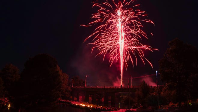 Fireworks explode in synchronization with patriotic music over the Oakes Street bridge at the 2017 July 3rd Pops Concert.