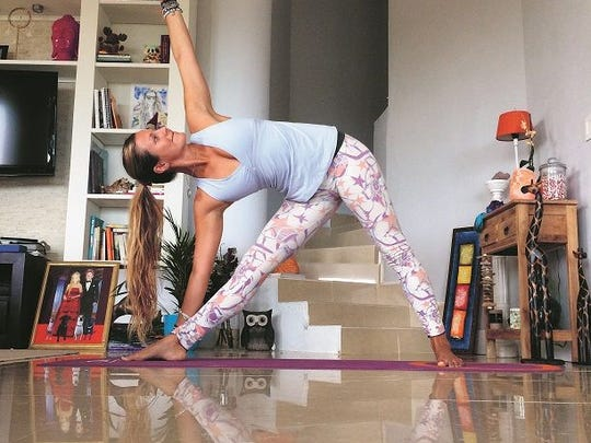 Rachel Brathen stretches out with a triangle pose while in her home in Aruba.